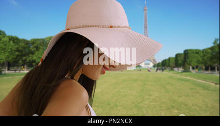 Close up of attractive Latina tourist looking around near Eiffel Tower smiling - Stock Photo