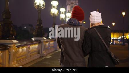 Rear view of happy couple on the Pont Alexandre III Bridge at night - Stock Photo