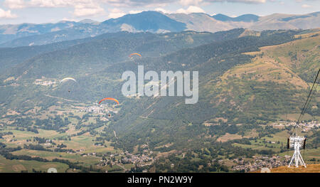 Saint Lary Soulan, France - August 20, 2018: several pair paragliders flying over the valley on a summer day - Stock Photo