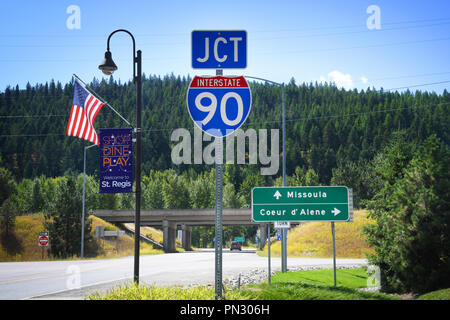 ST. REGIS, MONTANA, USA: September 1, 2018: An American flag and road and welcome signs at the juntion of Interstate 90 and Montana Highway 135 - Stock Photo