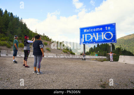 LOOKOUT PASS, IDAHO, USA - September 1, 2018: Family of five stop to take pictures at the Welcome to Idaho road sign - Stock Photo