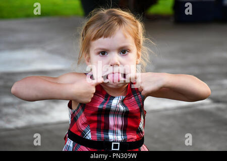 4-year-old girl making a silly face - Stock Photo
