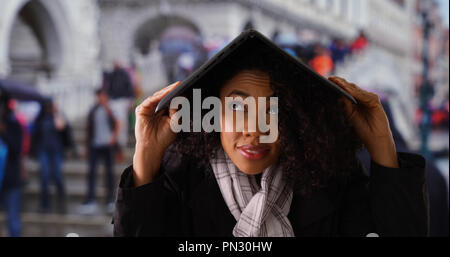Woman using laptop computer to protect herself from rain in Venice - Stock Photo