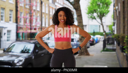 Cheerful smiling black female jogger in active wear standing on city street - Stock Photo