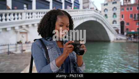 Attractive black woman takes photo of scenic Grand Canal in Venice with camera - Stock Photo