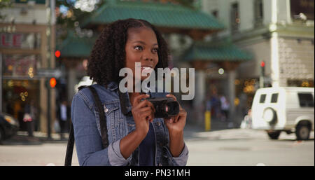 Attractive black woman takes picture near Chinatown entrance in San Francisco - Stock Photo