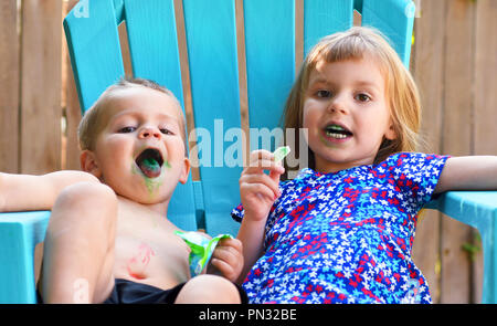 Two toddlers eating candy with blue tongues - Stock Photo