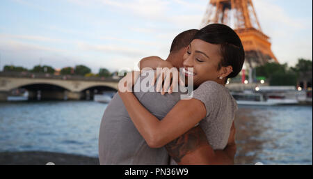 Tender African couple embracing by Seine River near Eiffel Tower - Stock Photo