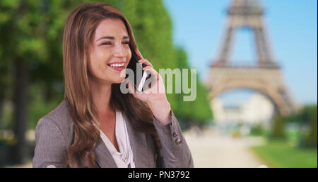 Brunette travelling in Paris talking on mobile phone near Eiffel Tower - Stock Photo