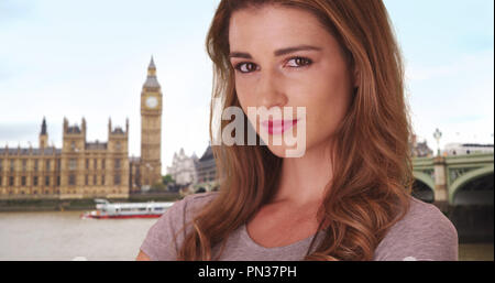 Pretty brown-haired white female smiling at camera in London near Big Ben - Stock Photo