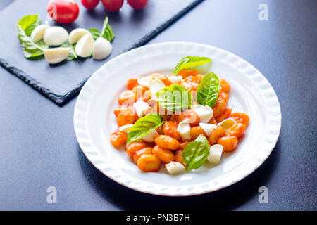 Cooked italian gnocchi from potatoes in tomato sauce with green fresh basil and mozzarella sliced balls served on a white plate with ingredients on bl - Stock Photo