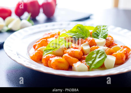 Gnocchi alla Sorrentina in tomato sauce with green fresh basil leaves and mozzarella balls served on a white plate on black background. Traditional it - Stock Photo
