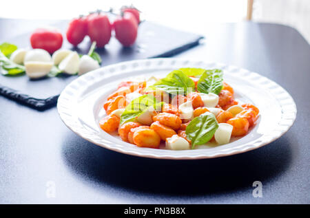 Gnocchi alla Sorrentina in tomato sauce with green fresh basil and mozzarella sliced balls served on a white plate with ingredients on black board bac - Stock Photo