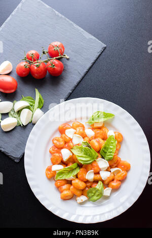 Potato gnocchi alla Sorrentina in tomato sauce with green fresh basil and mozzarella balls served on a plate and ingredients on shale board on black b - Stock Photo
