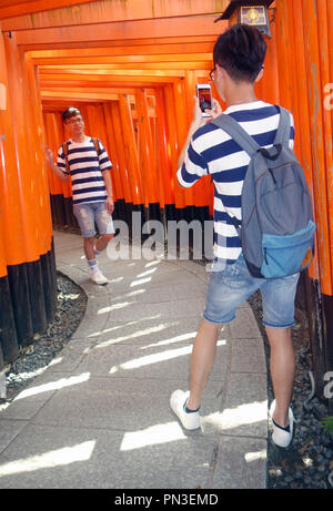Boys photographing each other between red torii gates, Fushimi Inari shrine, Kyoto, Japan. No PR or MR