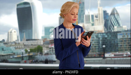 London businesswoman typing message on mobile phone - Stock Photo
