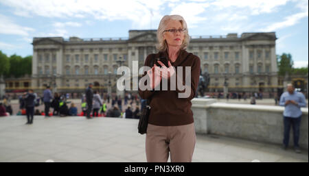 Senior woman tourist checking phone map or rideshare app on mobile in London - Stock Photo