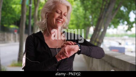 Mature woman jogger checks her heart rate - Stock Photo