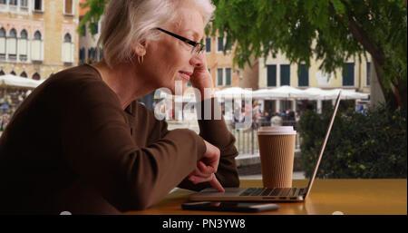 Senior woman tourist in Venice using laptop computer at Venice Cafe - Stock Photo