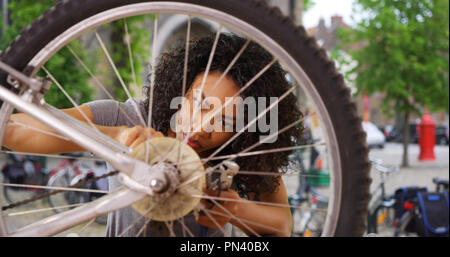 Close up of African woman fixing wheel or tire on bike while in city square - Stock Photo