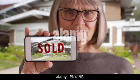 Elderly white woman holding phone with picture of home that was recently sold - Stock Photo