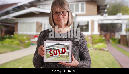 Senior Caucasian female holding tablet with picture of recently sold home - Stock Photo