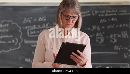 Independent senior woman teacher working on tablet device in front of chalkboard - Stock Photo
