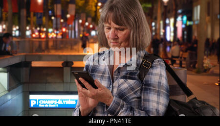 Confused senior woman using smartphone device for navigation on Champs-Elysees - Stock Photo