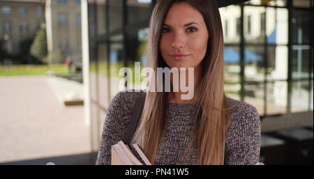 Portrait of smart young Caucasian female with books outside on university campus - Stock Photo