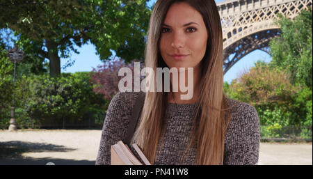 Confident female exchange student holding books posing near Eiffel Tower - Stock Photo