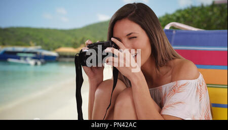 Millennial girl taking photo with camera while sitting at beach near some boats - Stock Photo