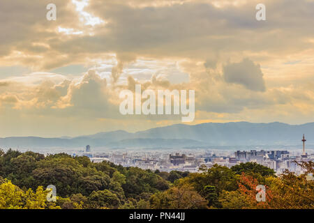 Sunbeams shining through the clouds over the city of Kyoto, Japan. View of Kyoto city from Kiyomizu temple with dramatic cloudy sky and sun beams on b - Stock Photo