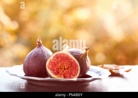 Closeup on fresh figs on dark shiny stone plate outdoors, toned image, text space - Stock Photo