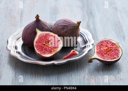 Fresh fruits - figs in metal plate on rustic wooden table - Stock Photo