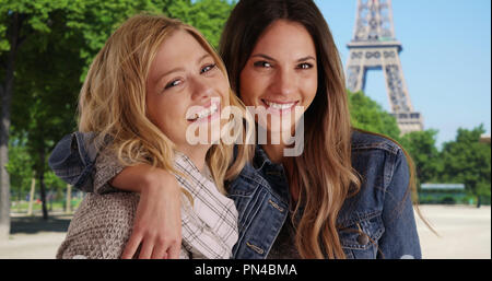 Pair of two female friends posing with joy outside near the Eiffel Tower - Stock Photo