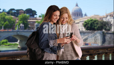 Couple of female tourists using map app with smartphone outside in Rome Italy - Stock Photo