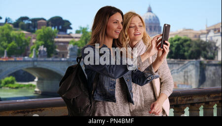 Couple of female tourists taking selfie with smartphone outside in Rome Italy - Stock Photo