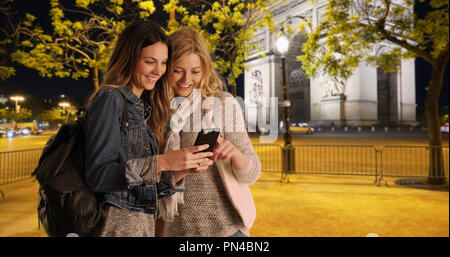 Two white female millennial tourists checking map app near Arc de Triomphe - Stock Photo