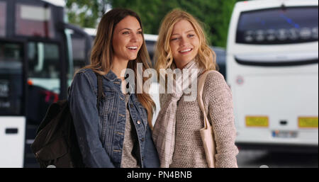 Attractive brunette with blonde female friend chatting near some tour buses - Stock Photo
