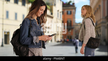 Attractive brunette female talking with friend while using smartphone in Rome - Stock Photo