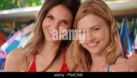 Pair of young white girls posing happily in front of shack of canoes at beach - Stock Photo