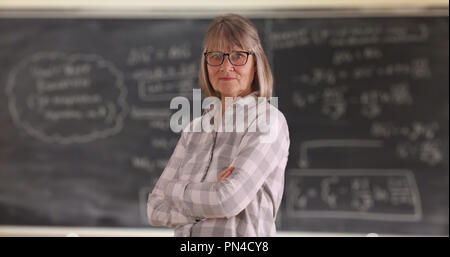 Confident senior woman teacher with arms crossed standing in front of chalkboard - Stock Photo