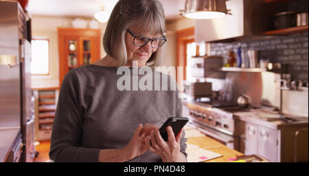 Happy senior woman sending text messages in domestic kitchen setting - Stock Photo