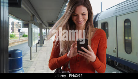 Young woman taking phone out of purse to send text while at train station - Stock Photo