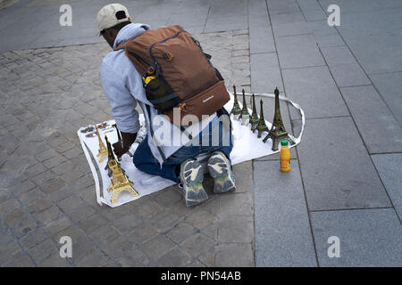Street vendor selling miniature Eiffel Towers in Paris, France - Stock Photo