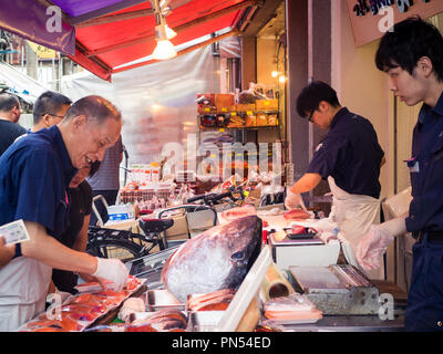 Fish mongers work with tuna at the Tsukiji Fish Market (Tsukiji outer market) in Tsukiji, Tokyo, Japan. - Stock Photo