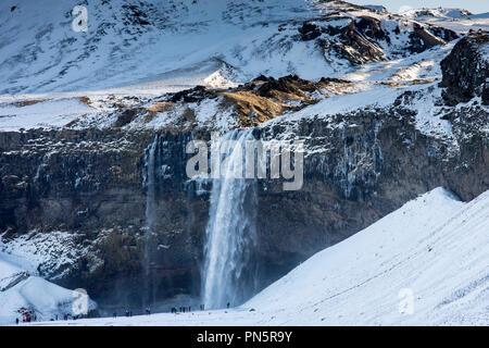 Tourists at spectacular Seljalands waterfall Seljalandsfoss in South Iceland with glacial melting waters from Eyjafjahajokull icecap - Stock Photo