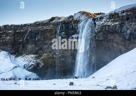 Tourists at spectacular waterfall Seljalandsfoss in South Iceland with glacial melting waters from Eyjafjahajokul icecap - Stock Photo