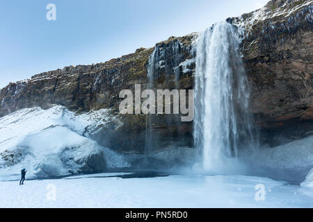 Tourist taking photograph at spectacular waterfall Seljalandsfoss in South Iceland - Stock Photo