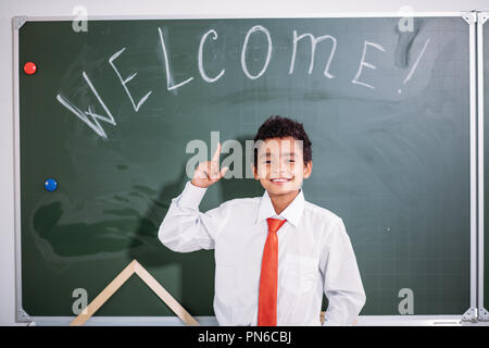 african school boy standing against chalk board with welcome word and looking at camera - Stock Photo